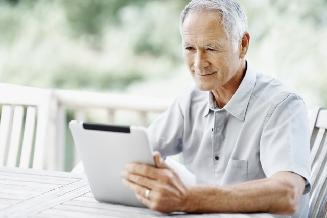 Portrait of a happy elderly man sitting on wooden bench while holding a tablet PC